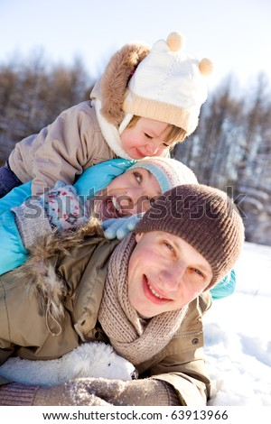 Happy young family enjoying their winter weekend - stock photo