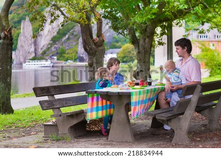 Happy young family, father with three children - boy, toddler girl and little baby enjoying  picnic sitting on a bench having fruit and sandwich for lunch outdoors during a trip to Dinant, Belgium