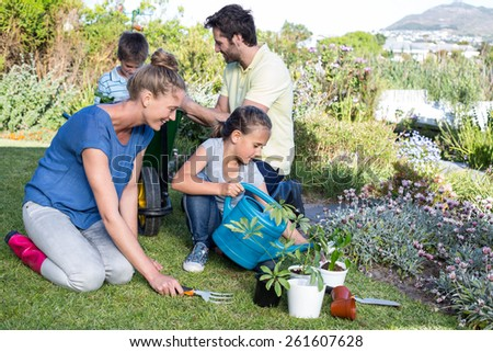Happy young family gardening together in the garden
