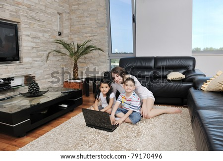 happy young family have fun and working on laptop at modern  home livingroom indoor