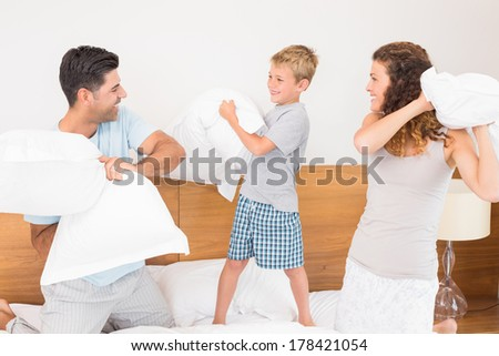 Happy young family having a pillow fight at home in bedroom - stock photo