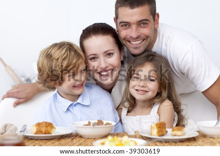 Happy young family having breakfast in kitchen