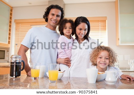 Happy young family having breakfast in the kitchen together
