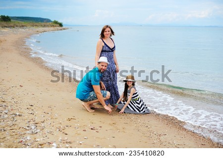 Happy young family having fun on the beach - stock photo