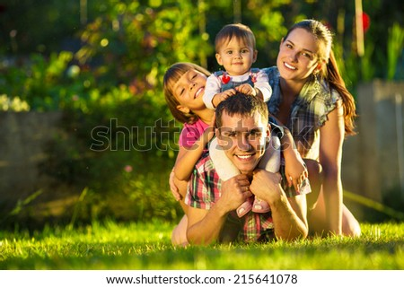 Happy young family having fun outdoors in summer. Mother, father and their cute little daughters are playing in the sunny garden. Happy parenthood and childhood concept. Focus on the father. - stock photo