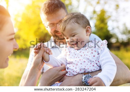 Happy young family having fun outside in spring nature - stock photo