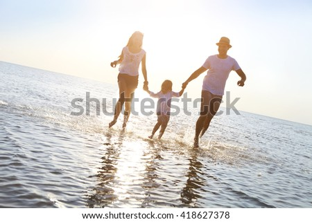 Happy young family having fun running on beach at sunset. Family traveling concept - stock photo