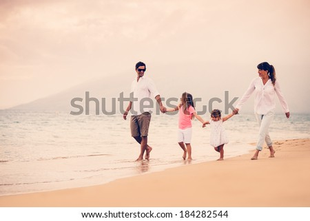 Happy Young Family Having Fun Walking on Beach at Sunset - stock photo