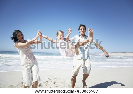 Happy Young Family Having Fun Walking on Beach in summer vacation day