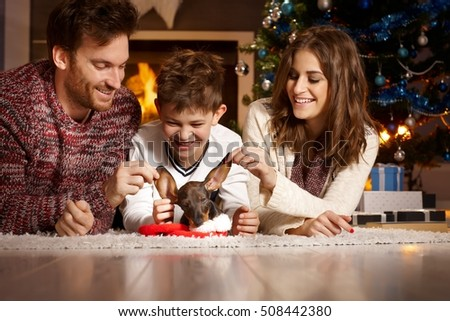 Happy young family having fun with dachshund puppy, lying on floor by christmas tree.