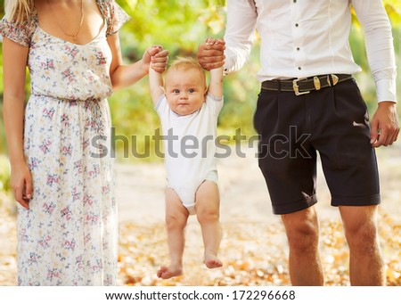 Happy young family holding a smiling 7-9 months old baby  - stock photo