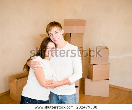 happy young family hugging on a background of cardboard boxes