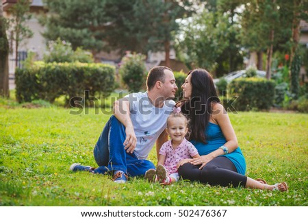 Happy young family in anticipation of the second baby. Pregnancy, health, walk outdoors in summer