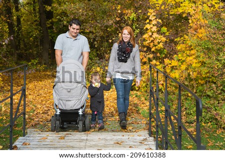Happy young family in autumn making together a walk in the nature. - stock photo