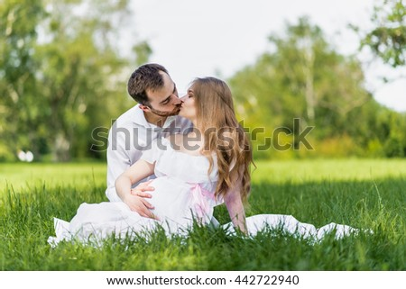 Happy young family in the park. Woman is pregnant.