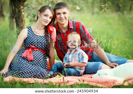 Happy young family is having fun in the green summer park outdoo