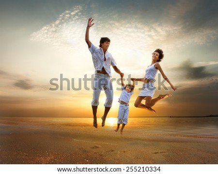 Happy young family jumping on sea shore at sunset  - stock photo