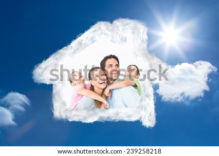 Happy young family looking up together against bright blue sky with clouds - stock photo