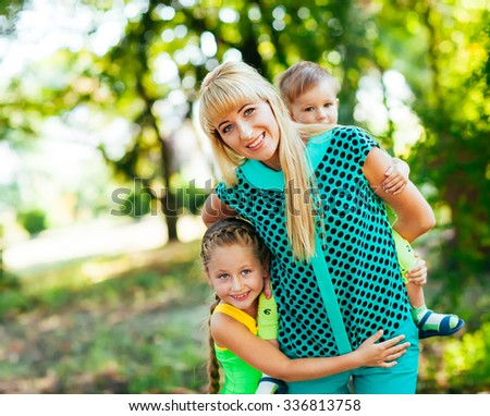 Happy young family, mother and childrens together having fun outdoors on the nature - stock photo