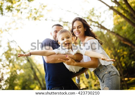 Happy young family. Mother and father make their happy  son to fly. - stock photo