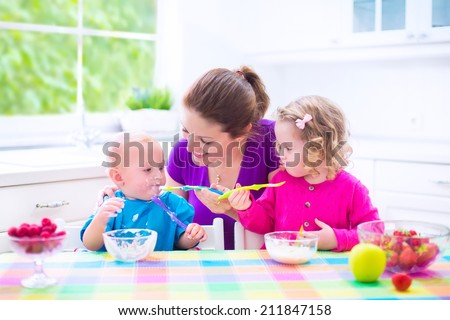 Happy young family, mother with two children, adorable toddler girl and funny baby boy having healthy breakfast eating fruit and dairy, sitting in a white sunny kitchen with window - stock photo