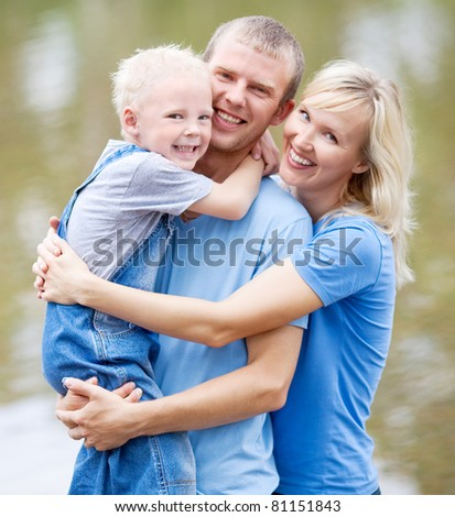 happy young family  near the lake outdoor on a summer day