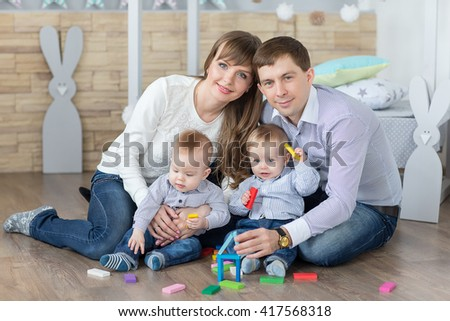 Happy young family of father, mother and twins are built of wooden planks toy house. - stock photo