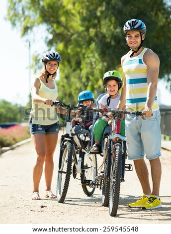 Happy young family of four cycling on street road in summer day - stock photo