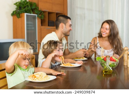 Happy young family of four eating spaghetti at home interior. Focus on girl
