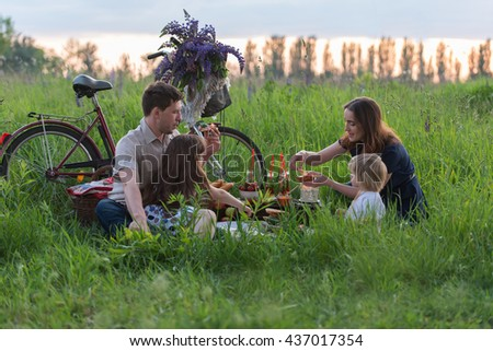 Happy young family of four having picnic at meadow at summer day - stock photo