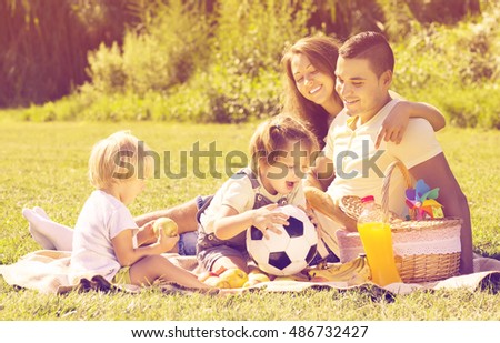 Happy young family of four having picnic at meadow. Focus on man