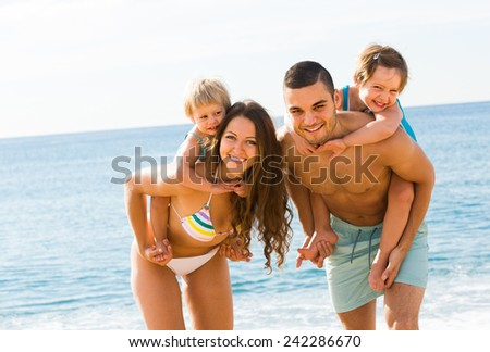 Happy young family of four in vacation at sea shore - stock photo