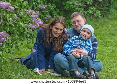 Happy young family of three have a rest in lilac garden