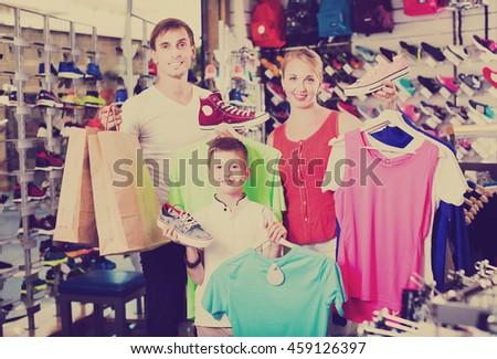 Happy young family of three picking various clothing in sport department