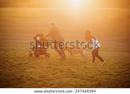 Happy young family on a walk outside on a green meadow at the sunset. - stock photo