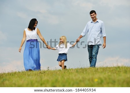 Happy young family on green summer grass meadow having fun