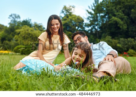 Happy Young Family On Picnic In Park. Smiling Parents And Children Having Fun, Playing, Spending Leisure Time Together In Nature. Kids And Adults Relaxing Outdoors On Weekend. Relationships Concept