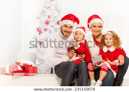 Happy young family opening presents on Christmas - stock photo