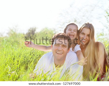 Happy young family outdoors in spring day - stock photo
