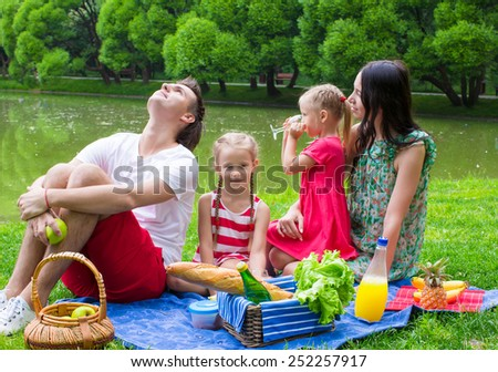 Happy young family picnicking outdoors near the lake