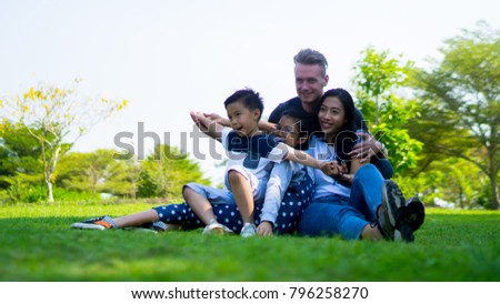Happy Young family play and enjoy with children having fun in nature park