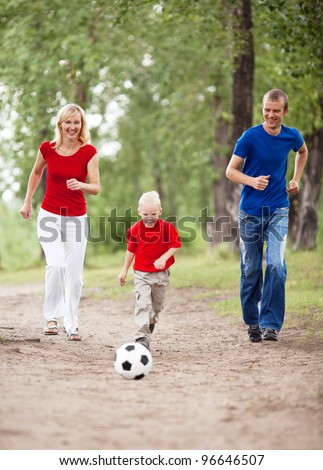 happy young family playing football outdoor on a summer day  (focus on the child) - stock photo