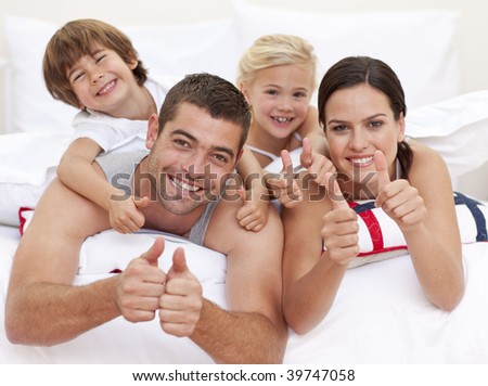 Happy young family playing in bed with thumbs up - stock photo