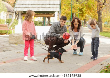 Happy young family playing puppy in the park. Shallow focus. - stock photo