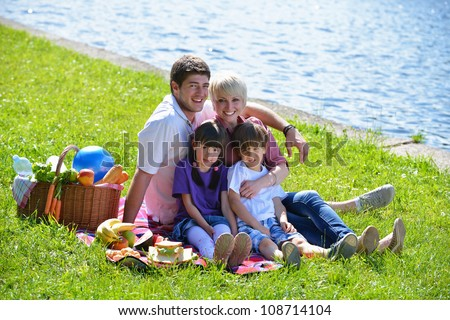 Happy young  family playing together with kids and eat healthy food  in a picnic outdoors - stock photo