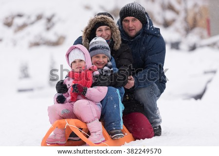 happy young family portrait on winter vacation while sitting sledge at  landscape with fresh falling snow - stock photo