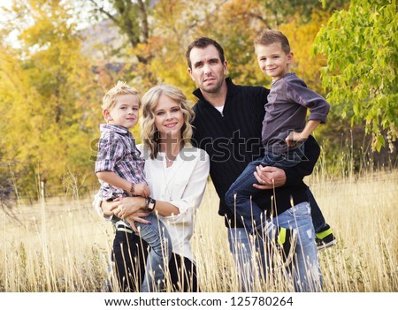 Happy Young Family Portrait with Fall colors - stock photo