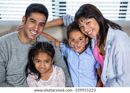 Happy young family posing together on the couch in living room
