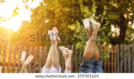 Happy young family showing legs outside in green nature. - stock photo