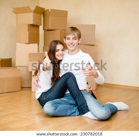 happy young family showing thumbs up on a background of cardboard - stock photo